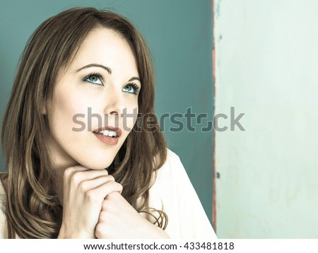 Creative Toned Portrait of a Happy Smiling Relaxed Young Caucasian Woman Resting Her Chin On Her Hands Looking Up - stock photo