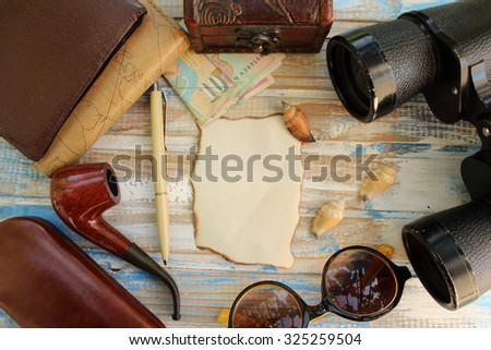 Creative travel background - binoculars, sunglasses, notebook, smoking pipe, wallet, sunglasses  case, box, money and copy space