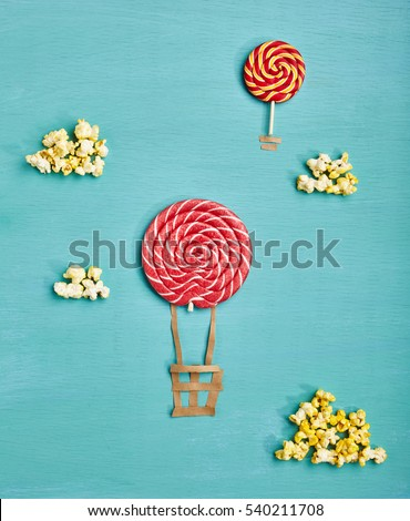 Creative Travel Concept - Top View Sweet Red Candy Air Balloons and Popcorn Clouds on Blue Background. Minimal Travel and Food Fun Concept. Flat Lay