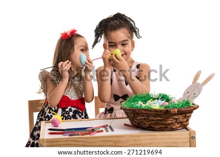 Creative two sisters painting easter eggs and sitting together at table - stock photo