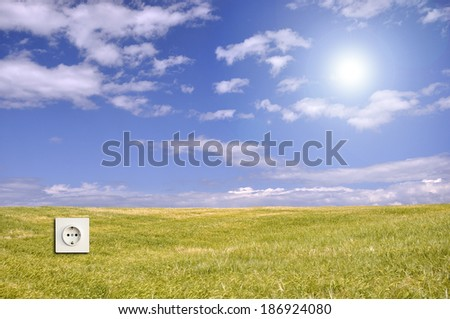 Creative use of lens flare for Green energy concept with landscape wallpaper and electric outlet - stock photo
