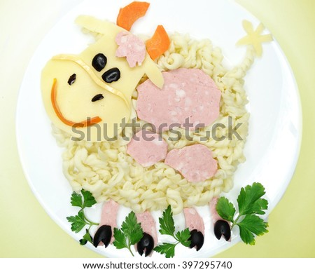 creative vegetable food meal with spaghetti and sausage cow form - stock photo
