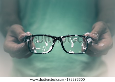 Creative vision concept. Closeup of creative man showing his stained eyeglasses. - stock photo