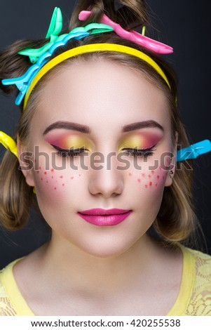 Creative woman lady girl model play with blue pink yellow orange colors. Bright conceptual art make-up glows light party time. Multicolored pins, clamps, clips on blond hair. Positive good lifestyle - stock photo