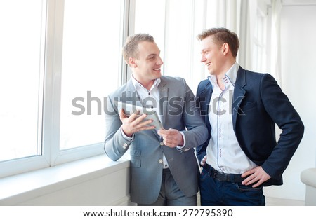 Creative work and technology. Two smiling handsome men using tablet computer while discussing something near window in office. - stock photo