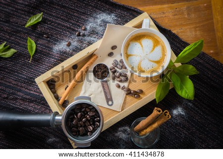 Creative work with a cup of boiling water in his hands. A handful of coffee, green, ground and soluble coffee leaves on a wooden table top white, black and white coffee beans Bank - stock photo