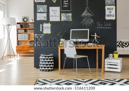 Creative working space with computer desk and accessories in flat with blackboard wall