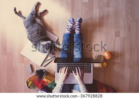 Creative workspace: girl working at the computer assisted by her cat. - stock photo