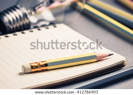 Creative writing, closeup pencil on notebook with light bulb on background