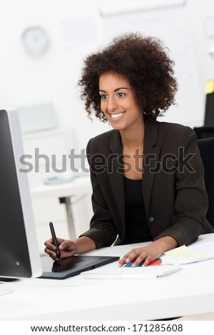 Creative young mixed race woman smiling while working as a designer at her desk, on a graphic tablet in front of a big monitor - stock photo