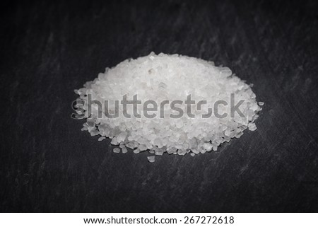 Creatively and Selectively Lit a Pinch of Rock Salt against a Black Background   - stock photo