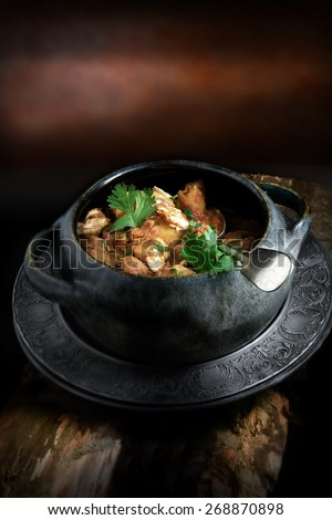 Creatively lit bowl of cooked Indian chicken curry with coriander garnish against a rustic background with copy space. The perfect image for your indian menu cover design. - stock photo