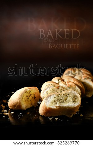 Creatively lit close up image of fresh crusty garlic bread baguette with butter and herbs against a rustic background setting. Generous accommodation for copy space. - stock photo