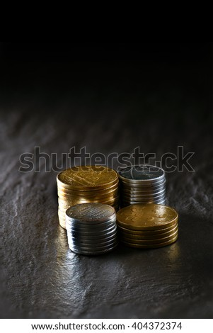 Creatively lit concept image for pension fund, investments, and savings. Stacked gold and silver coins against a dark background on oiled slate. Copy space. - stock photo