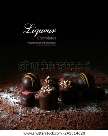Creatively lit dark liqueur chocolates against a dark background. Copy space. - stock photo