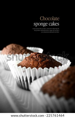 Creatively lit home-baked chocolate muffins with selective focus against a black background. Copy space. - stock photo