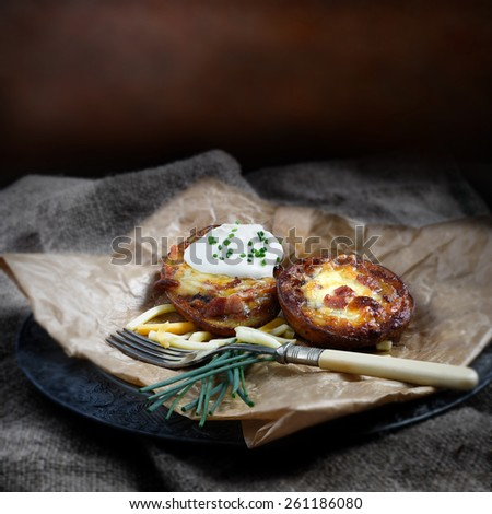 Creatively lit loaded cheese and bacon potato skins with Creme Fresche and chive garnish against a rustic background on hessian matting. Square crop. Copy space. - stock photo