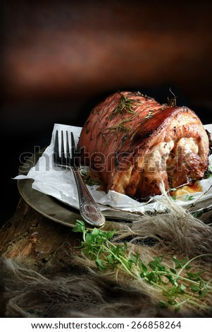 Creatively lit pork roast joint with rosemary, thyme and lemon against a  rustic background with copy space. The perfect image for your Sunday lunch menu cover design. - stock photo