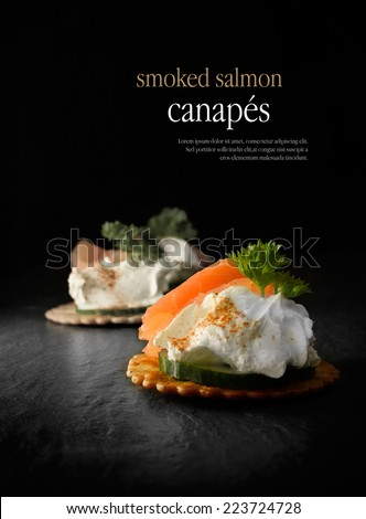 Creatively lit smoked salmon canapes against a black background. Copy space. - stock photo