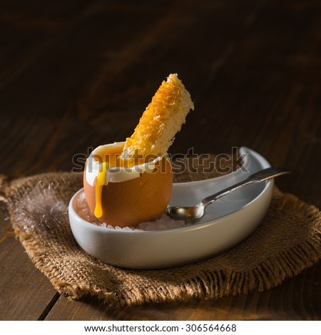 Creatively lit soft boiled egg with bread slice - stock photo