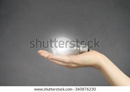 Creativity concept. Hand holding a glowing light bulb. - stock photo