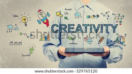 Creativity concept with young man holding a tablet computer  - stock photo