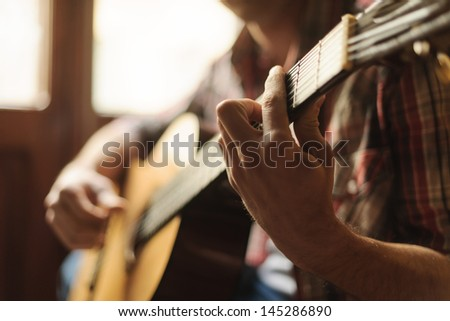 Creativity in focus. Close-up of men playing acoustic guitar - stock photo