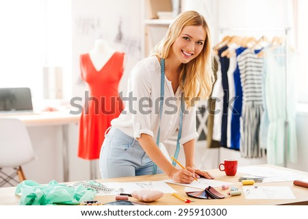 Creativity never goes out of style. Smiling of young woman drawing and looking at camera while leaning at her working place in fashion workshop