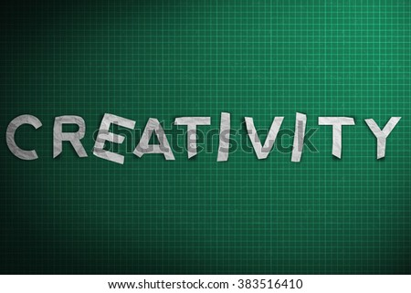 Creativity word made with paper on green grid background.