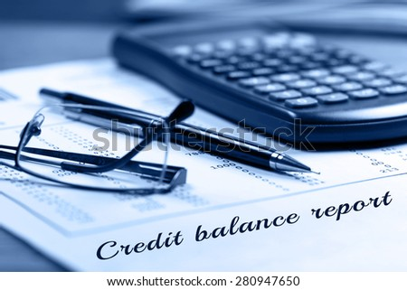 Credit balance report.  Calculator, glasses and black pen on financial documents in the background.  - stock photo