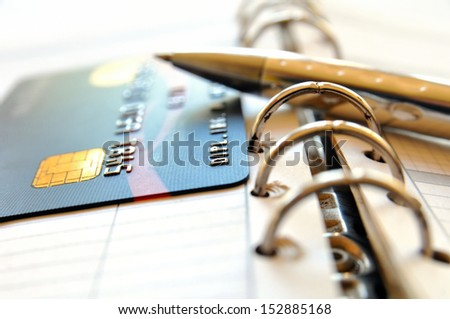 Credit card and ball pen on a organizer - stock photo