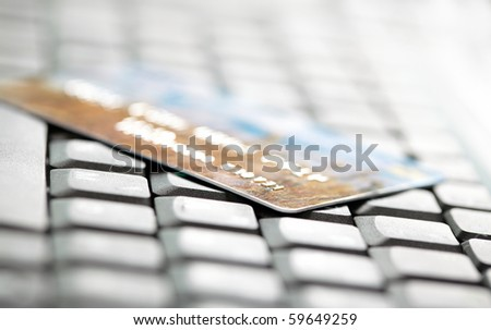 Credit card and laptop. Shallow DOF - stock photo