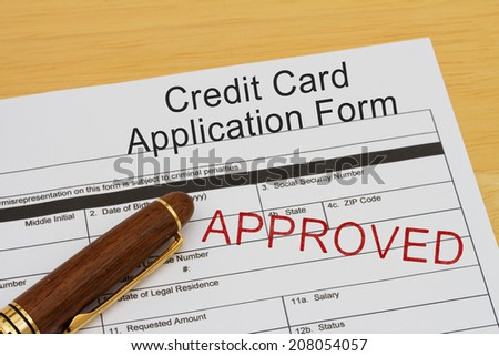 Credit Card Application Form with an approved stamp and a pen on a wooden desk
