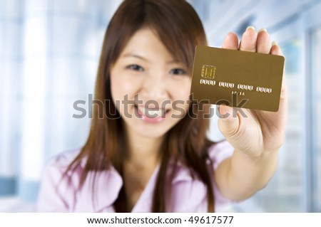 Credit card. Asian woman holding a credit card, focus on the card. Card number and expiry date created by my own. - stock photo