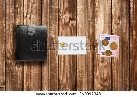 Credit card, cash euro and wallet on wooden table