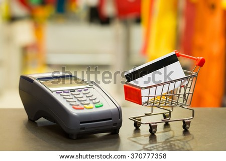Credit Card In Shopping Cart With Credit Card Machine In Store : Selective Focus On Credit Card - stock photo