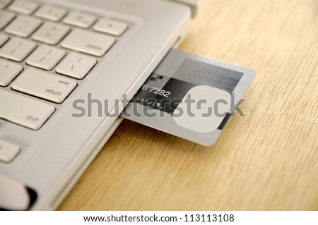 Credit card insert inside laptop on the wooden desk - stock photo