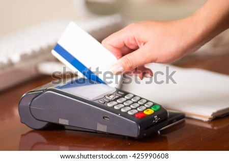 Credit card machine close up, white card with blue band swiping in the machine, woman hand - stock photo