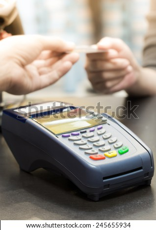 Credit Card Machine on the Table with Woman handing over credit card to Cashier in Background - stock photo