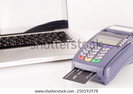 Credit Card Machine with Laptop In Background - stock photo