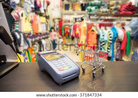 Credit Card Machine With Shopping Cart In The Store - stock photo