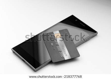 Credit card on mobile phone close up on monochromatic background, captured with small depth of field.  - stock photo