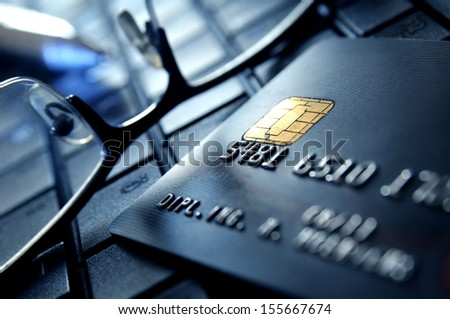Credit card with glasses on a laptop keypad - stock photo