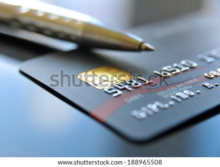 Credit card with silver colored ballpoint pen - stock photo