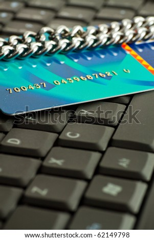 Credit card wrapped in a chain on notebook keyboard - stock photo