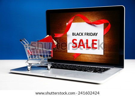 Credit cards in shopping cart and laptop, Black Friday Sale concept - stock photo