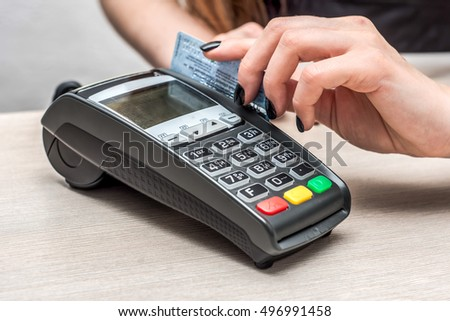 Credit or debit card password payment. Customer hand is entering personal identification number in shop or supermarket. Payment terminal keypad, pin. Close-up, selective focus.