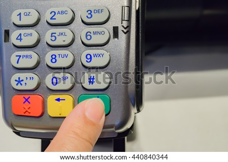 Credit or debit card password payment. Customer hand is entering pin in shop or supermarket. Payment terminal keypad, pin. Buy and sell products and service. Close-up, selective focus. - stock photo