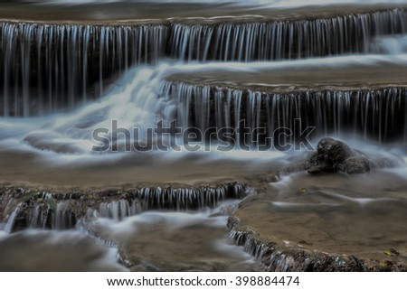 Creek or stream water flowing past rocks and stones - stock photo