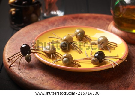 Creepy crawly edible Halloween spiders made from cured green and black olives with Italian spaghetti legs on a side table at a Halloween party for appetizers or favors for trick-ot-treating - stock photo